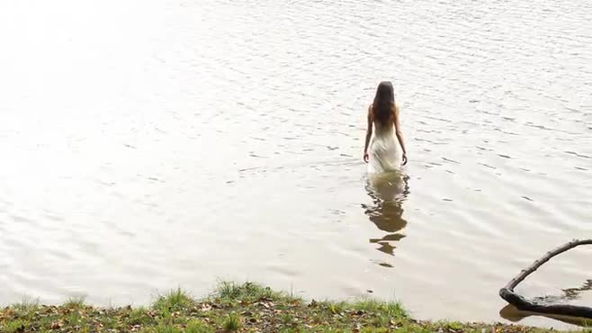 Footage of a girl in a white dress at and in a lake